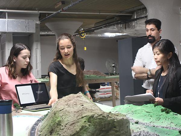 Magdalia Campobasso and Olivia Palmieri show their work to the judge's panel during the final round of the WE Design Competition.