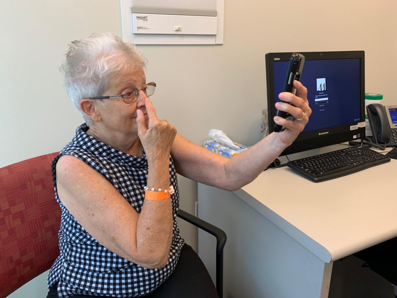 A female patient participates in a video screening test on a smartphone
