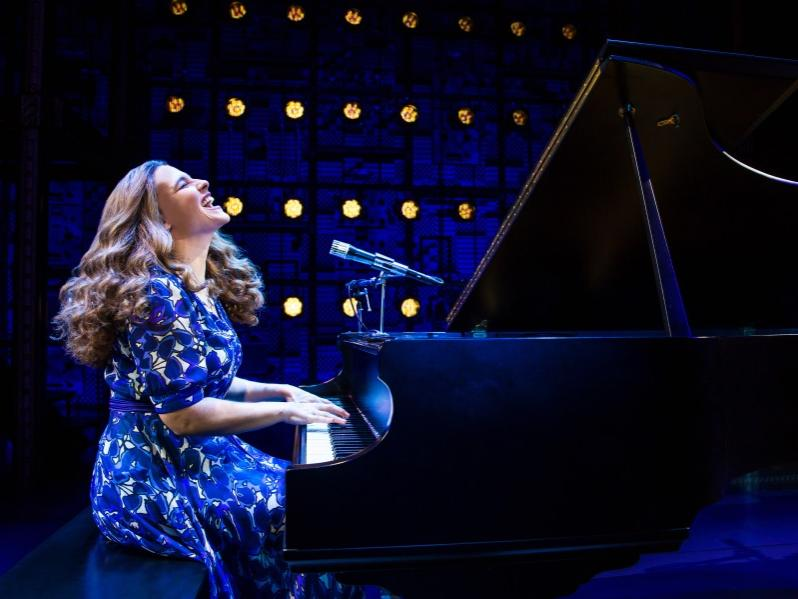 A woman throws her head back and sings while playing at a grand piano.