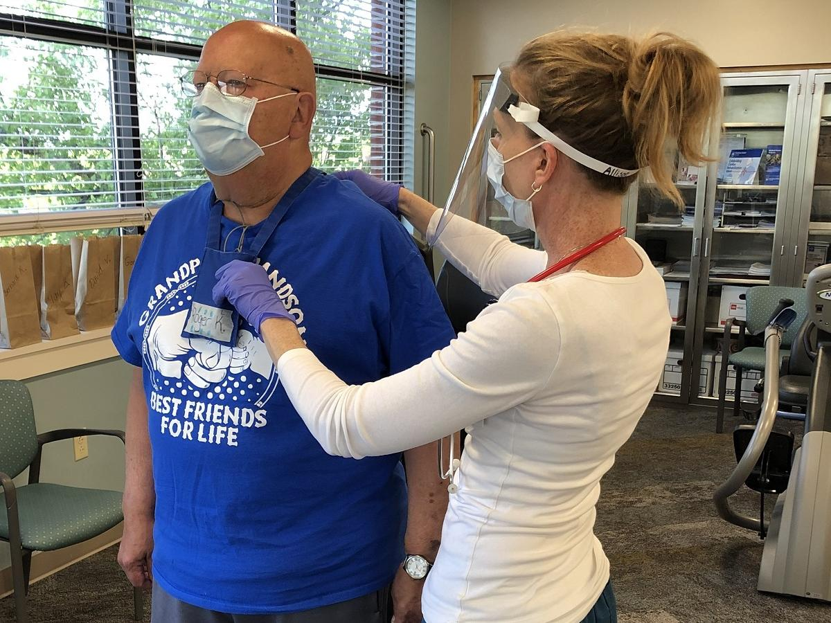 An exercise physiologist touches the back of a male patient as he stands in a cardiac rehabilitation room. The man is wearing a heart monitor and face mask. The exercise physiologist is wearing a face mask and face shield.