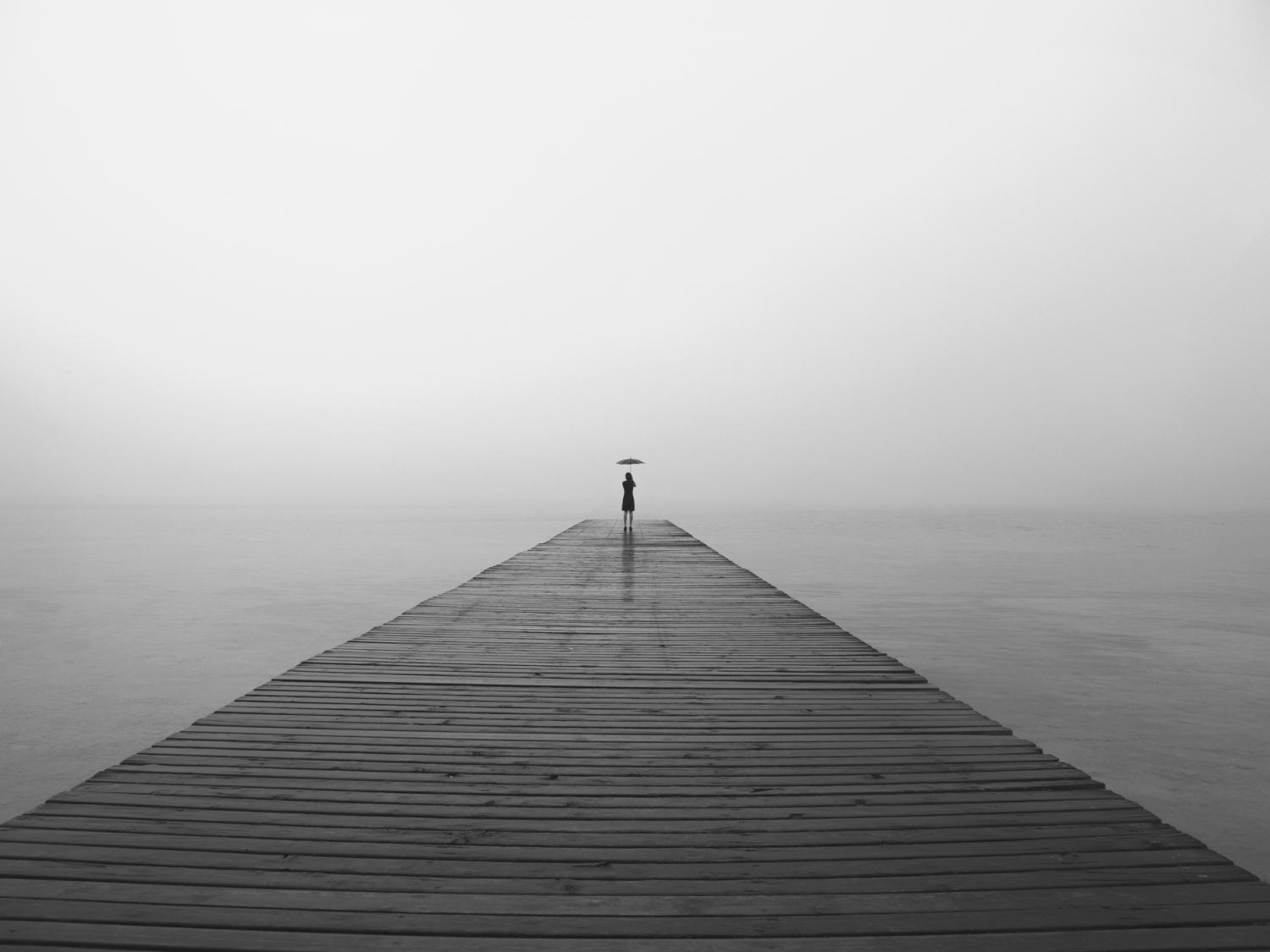 a long peer over water with a very small person at the very end with a black umbrella