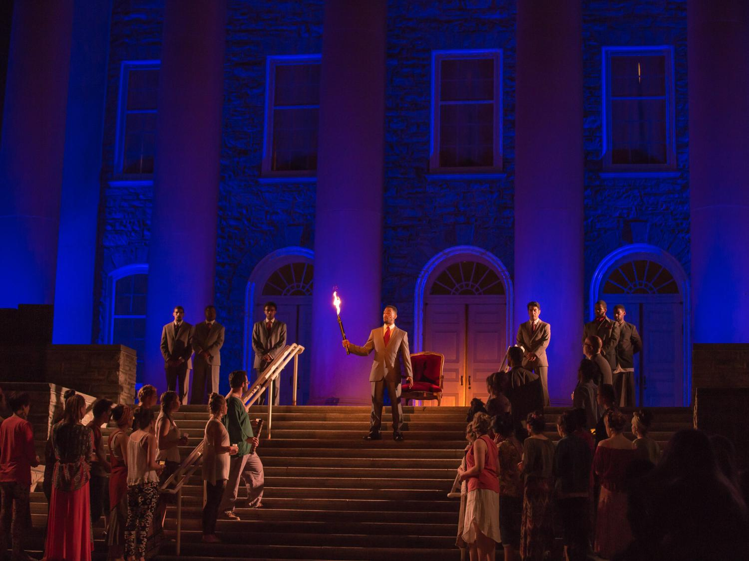 Penn State Theatre actors perform on the steps of the Old Main building.