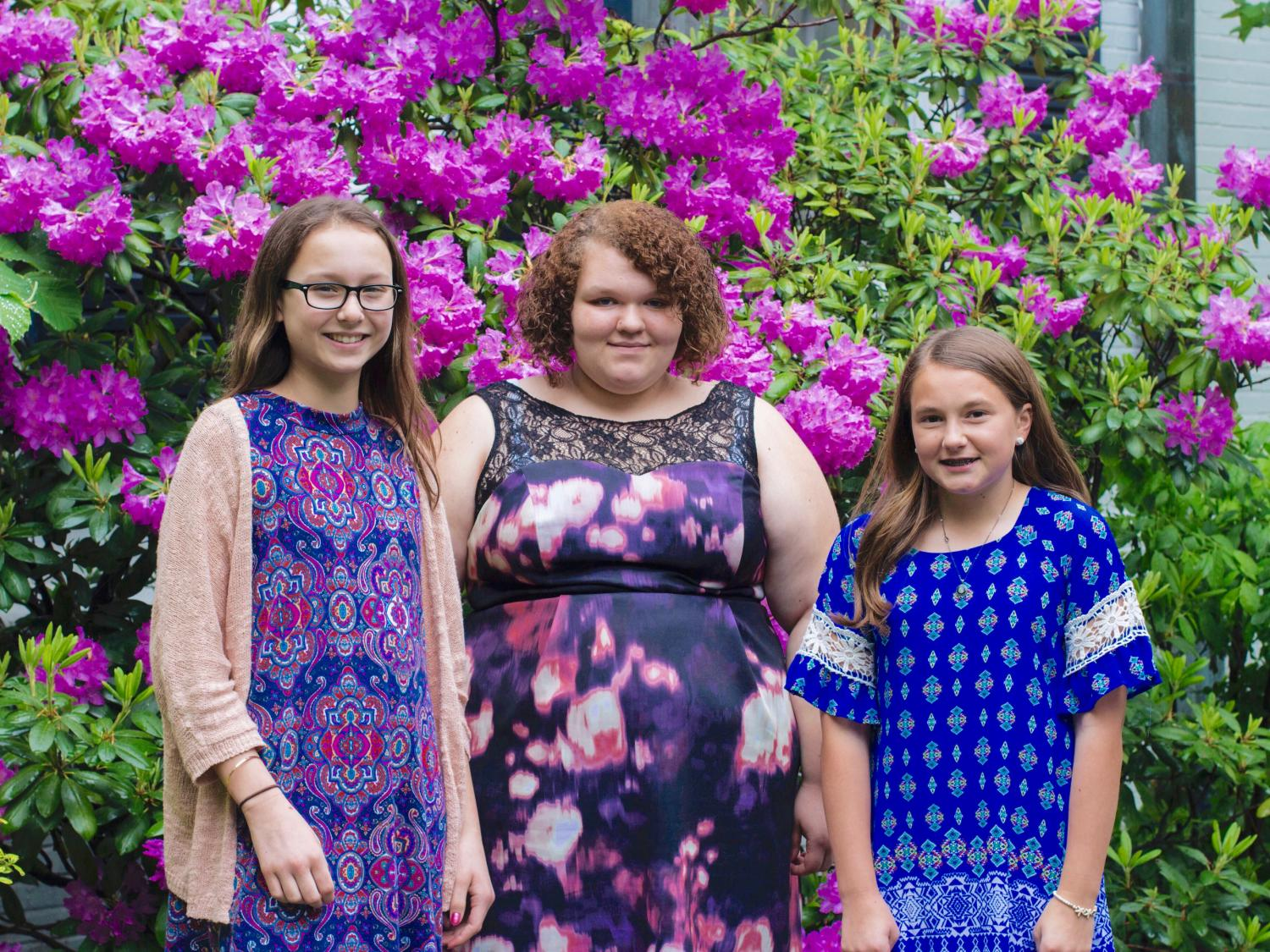 horizontal outdoor photo of three white female students standing in front of large blooming rhododendron shrub