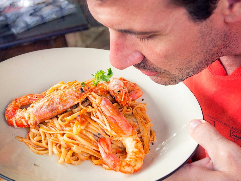 Man smelling pasta dish