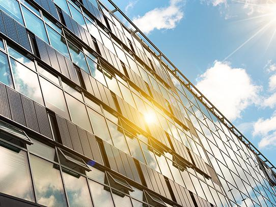 The sun shines on solar panels attached to a glass building.