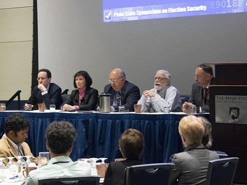 Five panelists sit at the front of a conference room