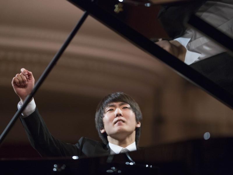 Seong-Jin Cho sits at a piano with his right armin midair.