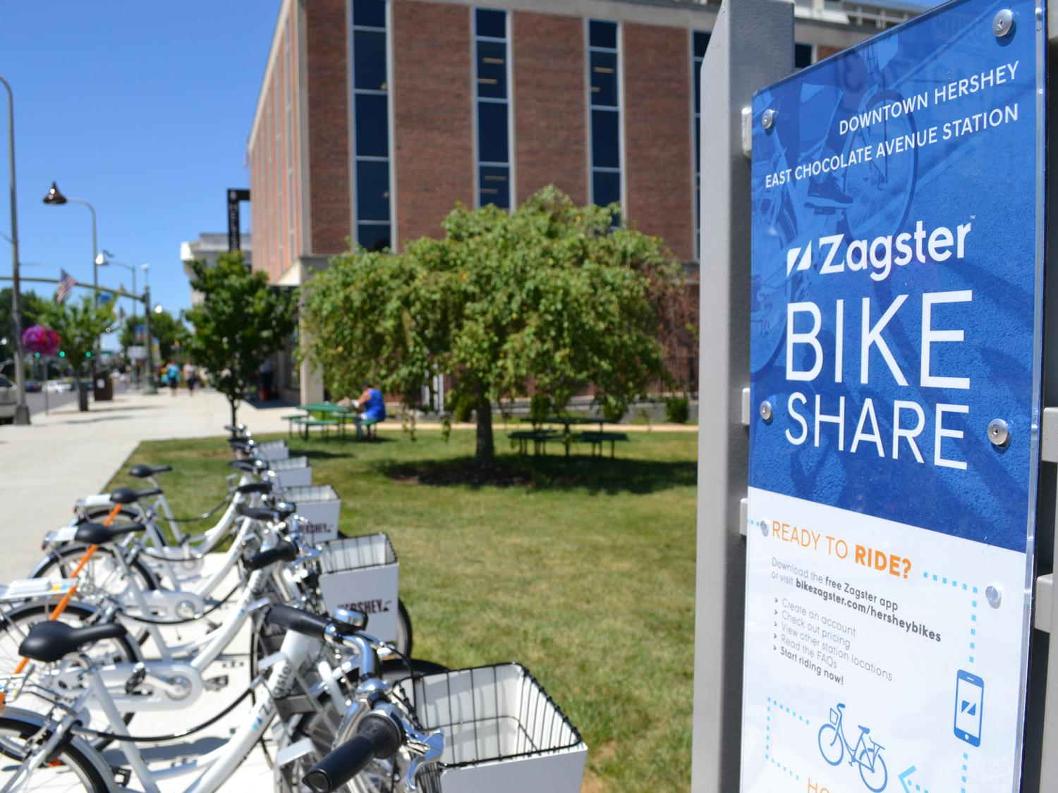 """Four bicycles are parked in parallel along a sidewalk. At right is a sign reading """"Downtown Hershey East Chocolate Avenue Station / Zagster Bike Share."""" A brick building with dark windows is in the background."""