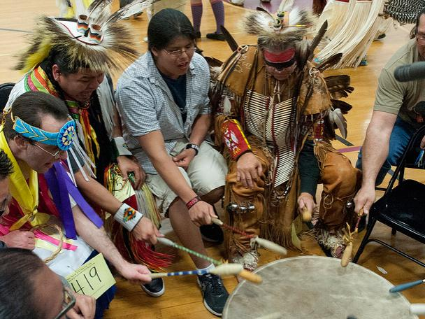American Indians in full dress gather around a drum during a powwow.