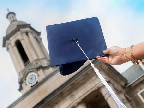 A hand holding a graduation cap in front of Old Main