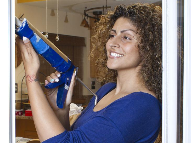 A woman stands with a caulking gun by a window