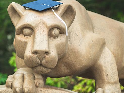 Nittany lion statue with navy graduation cap on its head